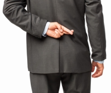 Rear view of a businessman crossing his fingers behind his back. Horizontal shot. Isolated on white.